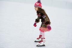 Entzückendes kleines Mädchen auf der Eisbahn Stockbild