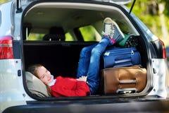 Entzückendes kleines Mädchen bereit, auf Ferien mit ihren Eltern zu gehen Scherzen Sie die Entspannung in einem Auto vor einer Au Lizenzfreie Stockfotos