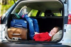 Entzückendes kleines Mädchen bereit, auf Ferien mit ihren Eltern zu gehen Scherzen Sie die Entspannung in einem Auto vor einer Au Lizenzfreie Stockfotografie