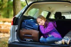 Entzückendes kleines Mädchen bereit, auf Ferien mit ihren Eltern zu gehen Scherzen Sie die Entspannung in einem Auto vor einer Au Stockfoto