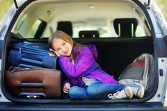 Entzückendes kleines Mädchen bereit, auf Ferien mit ihren Eltern zu gehen Scherzen Sie die Entspannung in einem Auto vor einer Au Lizenzfreie Stockbilder