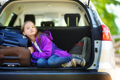 Entzückendes kleines Mädchen bereit, auf Ferien mit ihren Eltern zu gehen Scherzen Sie die Entspannung in einem Auto vor einer Au Lizenzfreies Stockfoto