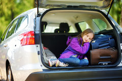 Entzückendes kleines Mädchen bereit, auf Ferien mit ihren Eltern zu gehen Scherzen Sie die Entspannung in einem Auto vor einer Au Stockbild