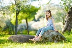 Entzückendes kleines Mädchen in blühendem Apfelbaumgarten am schönen Frühlingstag stockfotografie