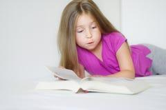 Entzückendes kleines Mädchen, das auf dem Bett liegt und ein Buch liest lizenzfreies stockfoto