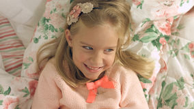 Entzückendes kleines Mädchen, das auf dem Bett liegt und fröhlich lacht Stockfotografie
