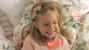 Entzückendes kleines Mädchen, das auf dem Bett liegt und fröhlich lacht Lizenzfreies Stockbild
