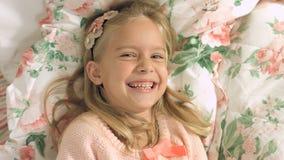Entzückendes kleines Mädchen, das auf dem Bett liegt und fröhlich lacht Lizenzfreie Stockfotos