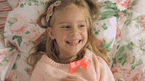 Entzückendes kleines Mädchen, das auf dem Bett liegt und fröhlich lacht Lizenzfreies Stockfoto