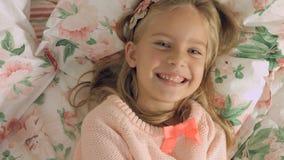 Entzückendes kleines Mädchen, das auf dem Bett liegt und fröhlich lacht Lizenzfreie Stockfotografie