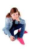 Entzückendes kleines Mädchen, das auf dem Boden mit Denimhemd sitzt Stockfoto