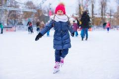 Entzückendes kleines Mädchen, das auf die Eisbahn eisläuft Lizenzfreies Stockbild
