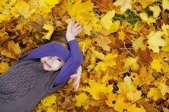 Entzückendes kleines Mädchen, das auf goldene Ahornblätter legt Stockbilder