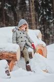 Entzückendes kleines Mädchen, das auf schneebedecktem Wald des hölzernen Anmeldungswinters sitzt Stockbild