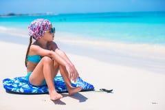 Entzückendes kleines Mädchen, das auf Surfbrett an der Küste sitzt Lizenzfreie Stockfotos