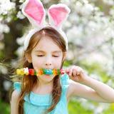 Entzückendes kleines Mädchen, das bunte Gummisüßigkeiten auf Ostern isst Lizenzfreies Stockbild