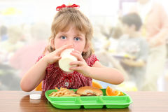 Entzückendes kleines Mädchen, das an der Schule zu Mittag isst Stockbild