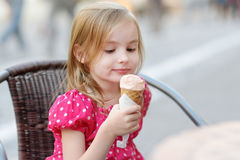 Entzückendes kleines Mädchen, das draußen Eiscreme isst Stockbilder