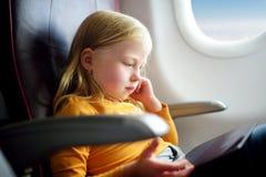 Entzückendes kleines Mädchen, das durch ein Flugzeug reist Kind, das durch Flugzeugfenster sitzt und eine digitale Tablette verwe Stockbild