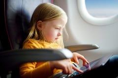 Entzückendes kleines Mädchen, das durch ein Flugzeug reist Kind, das durch Flugzeugfenster sitzt und eine digitale Tablette verwe Stockfoto