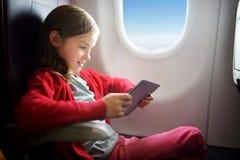 Entzückendes kleines Mädchen, das durch ein Flugzeug reist Kind, das durch Flugzeugfenster sitzt und eine digitale Tablette verwe Stockbilder