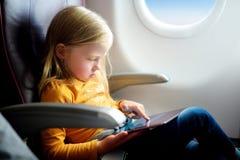 Entzückendes kleines Mädchen, das durch ein Flugzeug reist Kind, das durch Flugzeugfenster sitzt und eine digitale Tablette verwe Lizenzfreies Stockbild