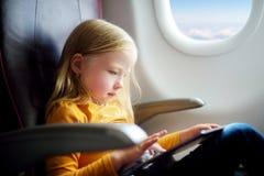 Entzückendes kleines Mädchen, das durch ein Flugzeug reist Kind, das durch Flugzeugfenster sitzt und eine digitale Tablette verwe Stockfotos
