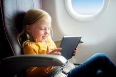 Entzückendes kleines Mädchen, das durch ein Flugzeug reist Kind, das durch Flugzeugfenster sitzt und eine digitale Tablette verwe Lizenzfreie Stockfotos