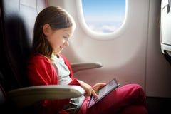 Entzückendes kleines Mädchen, das durch ein Flugzeug reist Kind, das durch Flugzeugfenster sitzt und eine digitale Tablette verwe Lizenzfreies Stockfoto