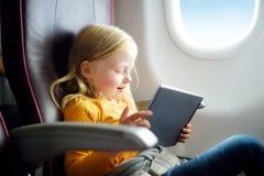 Entzückendes kleines Mädchen, das durch ein Flugzeug reist Kind, das durch Flugzeugfenster sitzt und eine digitale Tablette währe Lizenzfreie Stockfotos