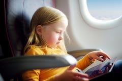 Entzückendes kleines Mädchen, das durch ein Flugzeug reist Kind, das durch Flugzeugfenster sitzt und eine digitale Tablette währe Lizenzfreies Stockbild