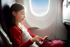 Entzückendes kleines Mädchen, das durch ein Flugzeug reist Kind, das durch Flugzeugfenster sitzt und eine digitale Tablette währe Stockfotografie