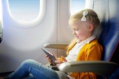 Entzückendes kleines Mädchen, das durch ein Flugzeug reist Kind, das durch Flugzeugfenster sitzt und eine digitale Tablette währe Stockfotos