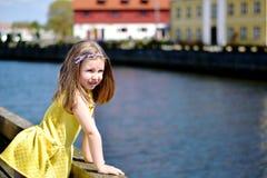 Entzückendes kleines Mädchen, das durch einen Fluss an einem schönen Sommertag spielt stockfotografie