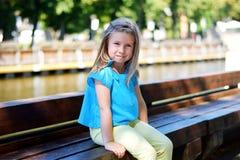 Entzückendes kleines Mädchen, das durch einen Fluss im sonnigen Park an einem schönen Sommertag spielt Stockbild