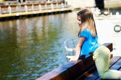 Entzückendes kleines Mädchen, das durch einen Fluss im sonnigen Park an einem schönen Sommertag spielt Lizenzfreies Stockfoto