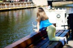 Entzückendes kleines Mädchen, das durch einen Fluss im sonnigen Park an einem schönen Sommertag spielt Lizenzfreies Stockbild