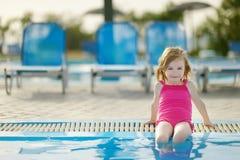 Entzückendes kleines Mädchen, das durch einen Swimmingpool sitzt Lizenzfreie Stockbilder