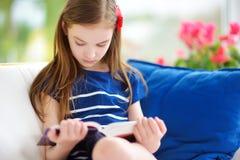 Entzückendes kleines Mädchen, das ein Buch im weißen Wohnzimmer am schönen Sommertag liest Lizenzfreies Stockbild