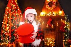Entzückendes kleines Mädchen, das ein magisches Weihnachtsgeschenk durch einen Weihnachtsbaum im gemütlichen Wohnzimmer im Winter stockfotografie
