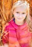 Entzückendes kleines Mädchen, das in einem Rosa lächelt Stockbild