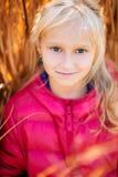 Entzückendes kleines Mädchen, das in einem Rosa lächelt Lizenzfreies Stockfoto