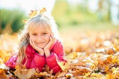 Entzückendes kleines Mädchen, das in einer rosa Jacke lächelt Stockfotos