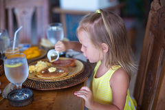 Entzückendes kleines Mädchen, das am Erholungsort frühstückt Lizenzfreies Stockbild
