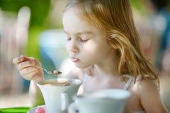 Entzückendes kleines Mädchen, das heiße Schokolade trinkt Stockbild
