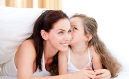 Entzückendes kleines Mädchen, das ihre Mutter küßt stockfoto