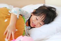Entzückendes kleines Mädchen, das im Bett mit ihrem Spielzeug liegt lizenzfreie stockbilder