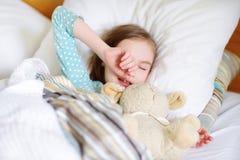 Entzückendes kleines Mädchen, das im Bett mit ihrem Spielzeug schläft Lizenzfreies Stockfoto
