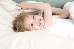 Entzückendes kleines Mädchen, das im Bett stillsteht Stockfotografie