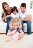 Entzückendes kleines Mädchen, das Münze in einem piggybank einsteckt Stockfoto